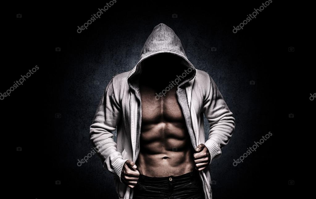 Strong athletic man on black background