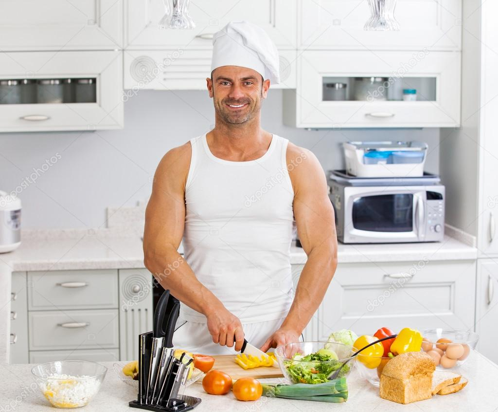 Happy handsome man cooking in kitchen at home. — Stock Photo © roman ...