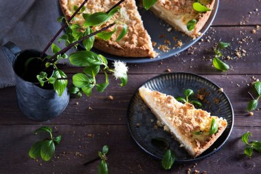 Beautiful and tasty curd pie on a wooden background surrounded by greenery. Spring breakfast, herbs, morning, homemade cakes. Selective focus.