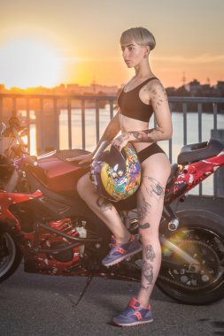 Girl with tattoos sitting on a motorcycle