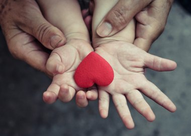 hand of a baby with red heart