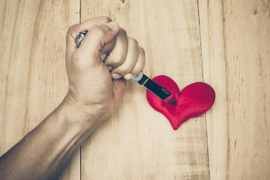 knife stabbing into a red heart