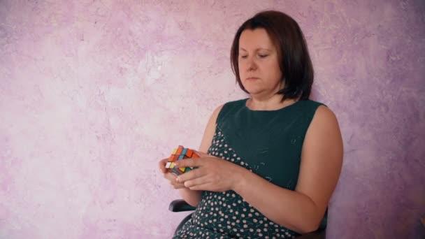 žena sedí shromažďovat Rubiks Cube