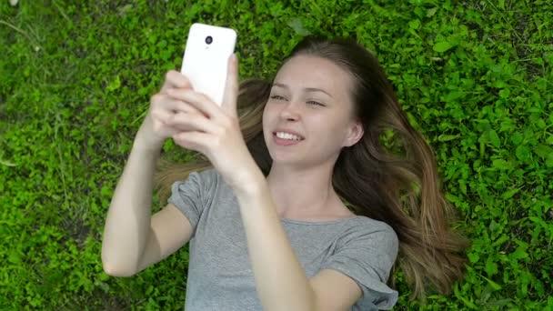 Dívka ležela na zelené louce na mobil