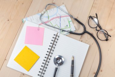 stethoscope , book note on wood