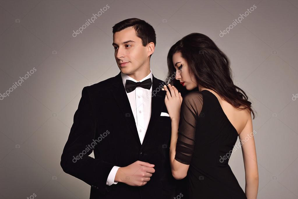 4e99deecd1836 Young couple of fashion models in classic clothes: black suit and bow tie,  evening dress on white background. Elegance style. Luxury. Sensuality.  Sexuality.