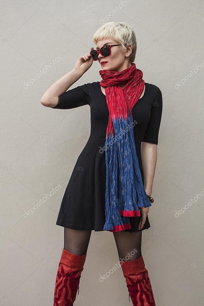 Élégante jeune femme belle blonde en noir peu robe, foulard rouge et  lunettes de soleil isolés sur fond gris. Fille aux cheveux courts. dd7227d0782
