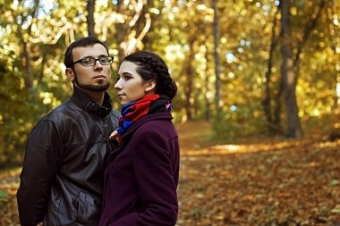 Young amorous couple handsome man and beautiful woman in autumn park. First date. Feelings amorousness, love, muse, dreaminess. Romance.