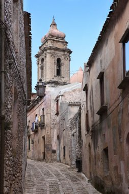 traditional narrow medieval street of Erice city with church