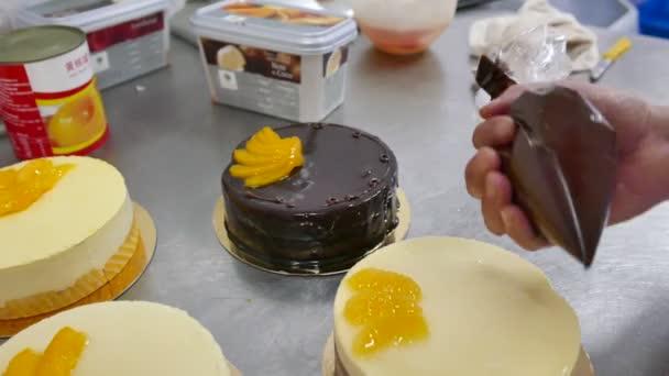Adding chocolate icing to baked sponge cake