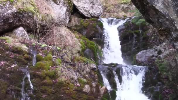 Mountain river waterfalls through boulders and rocks