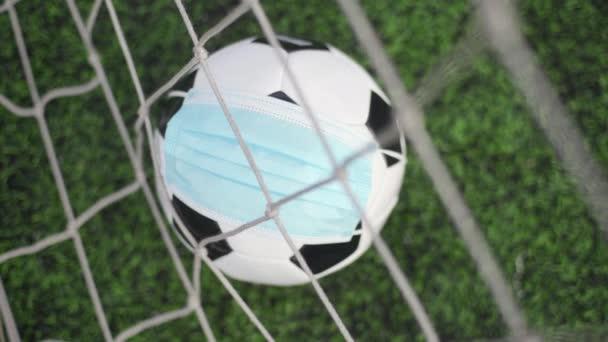 Fotbalový míč v lékařské masce na stadionu Green Grass. Míč v brankové síti. Fotbalové soutěže zastaveny