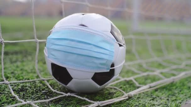 Fußball mit medizinischer Maske im Tornetz. Leeres Stadion. Absage von Fußballwettbewerben
