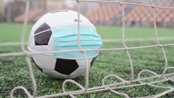 Focilabda orvosi maszkban a Goal Net-ben. Üres stadion. A labdarúgó-versenyek törlése