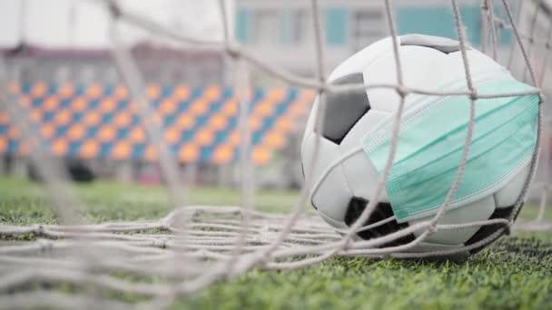 Fotbalový míč s maskou na prázdném stadionu. Černá a bílá koule v brankové síti, Pozadí plastových sedadel bez lidí. Záběry 4k