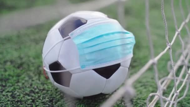 Fußball in medizinischer Maske auf dem grünen Rasen des Stadions. Ball im Tornetz. Fußballwettbewerbe abgebrochen