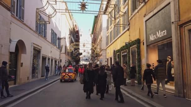 Řím, Itálie - 13. prosince 2020: Pohled na Via dei Condotti a Trinit dei Monti během epidemie Covid-19. Mnoho lidí, kteří nosí ochranné masky na vánoční nákupy.