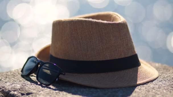 Žlutý klobouk a brýle na pozadí odlesků z vody