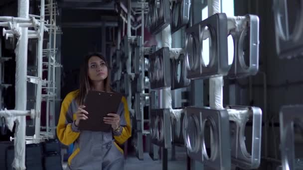 Eine junge hübsche weiße Frau arbeitet in der Lackiererei des Werks, sie überprüft die unbemalten Metallprodukte und führt eine Checkliste..