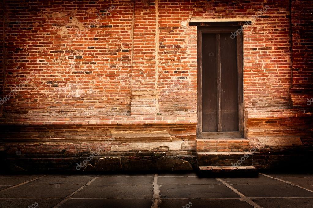 paredes de ladrillo rojo y puertas de madera antigua u foto de stock