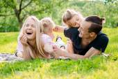 Rodina ležet na trávě v přírodě