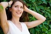 Portrét veselé ženy zvyšuje vlasy v horkém letním dni