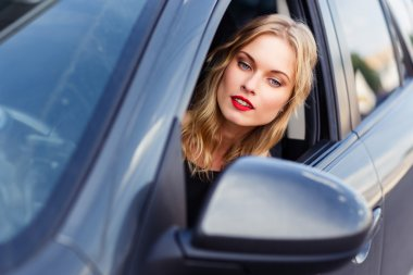 Gorgeous blonde woman behind the wheel looking in side mirror