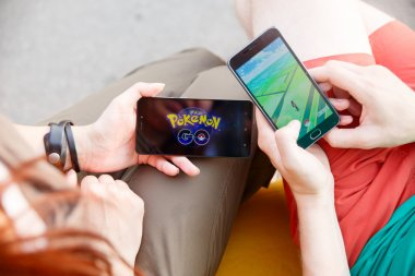 First man held phone in hands showing its screen with Pokemon Go app, second install that application.