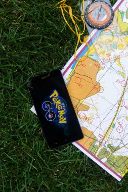 Phone with Pokemon Go application on screen, maps and compas.