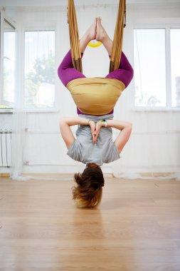 Antigravity yoga, woman in hammock and doing asana