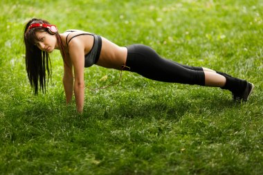 Beautiful strong active woman training push ups in park