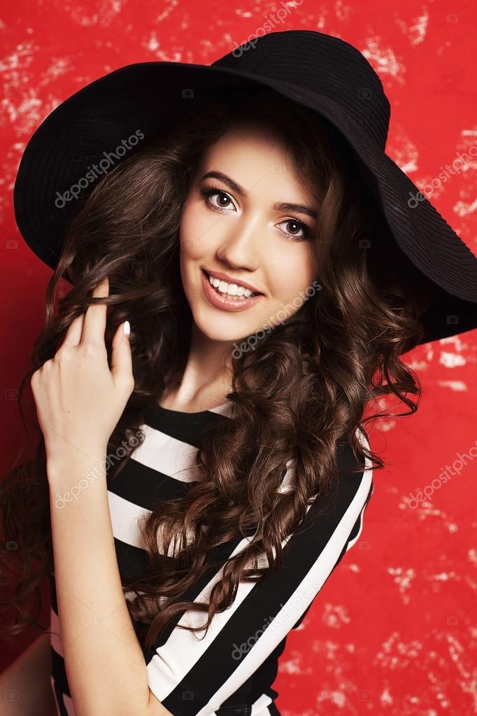 79cb114663e4 Ritratto di bella giovane donna con capelli ricci lunghi in cappello nero e  abito a righe su fondo rosso– immagine stock