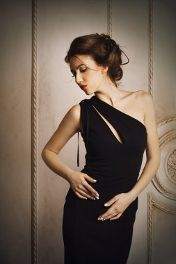 Elegant woman in black dress with beautiful hairstyle