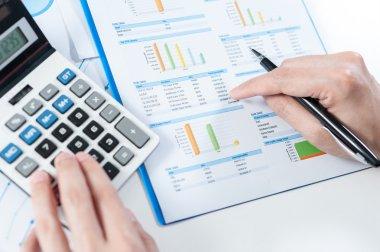 Businessman using calculator analyze report