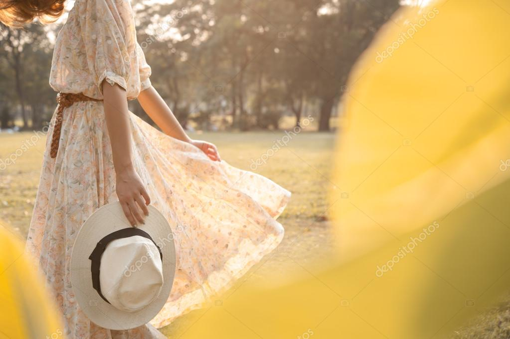 Beautiful young woman walk in park with hat