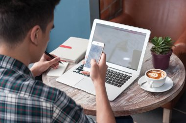 Businessman using smartphone and laptop writing on tablet on woo