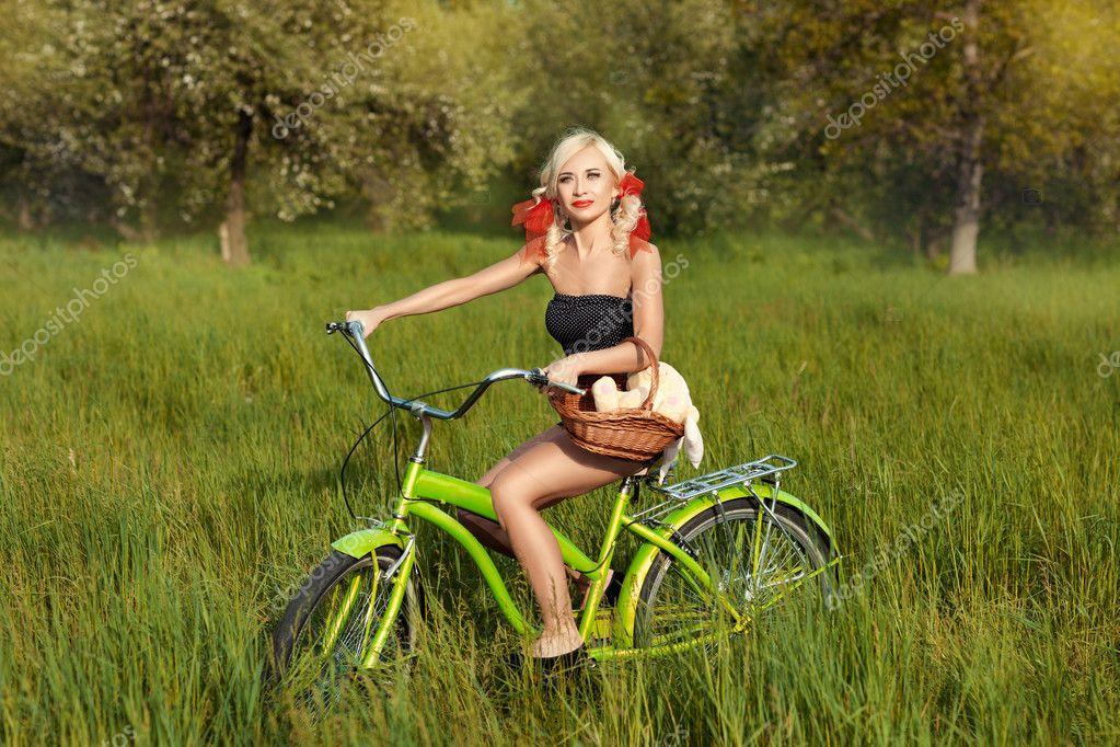 Playful mature woman riding bicycle on sunny beach grass path