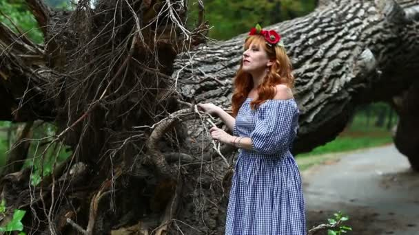 Dívka v věnec na pozadí padlý strom úsměvu.