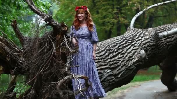 Dívka s věncem stojí poblíž kořeny padlého stromu.