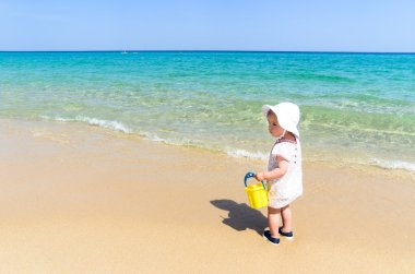 Adorable little girl in swimsuit having fun at tropical sandy beach