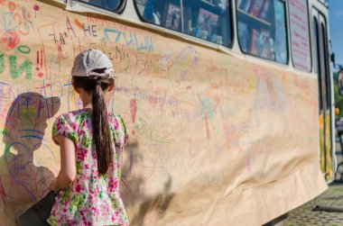 Rear view of cute little girl drawing a picture on the wall