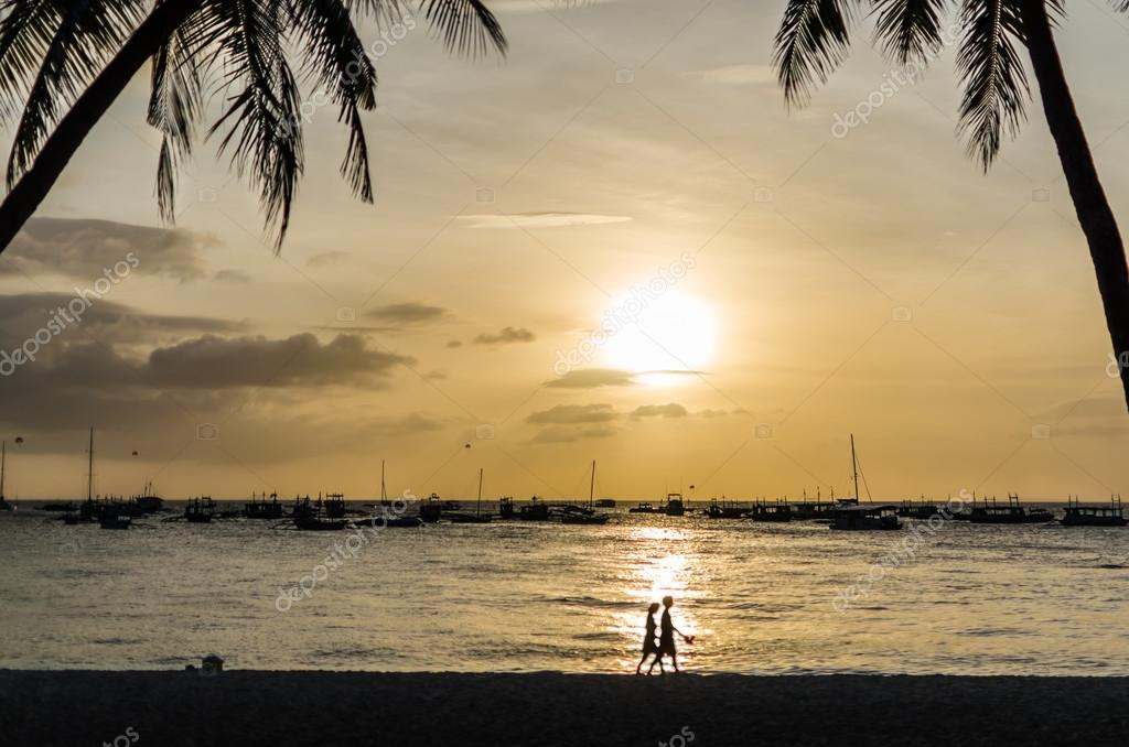 Sailing boats and silhouette of couple against a beautiful sunset