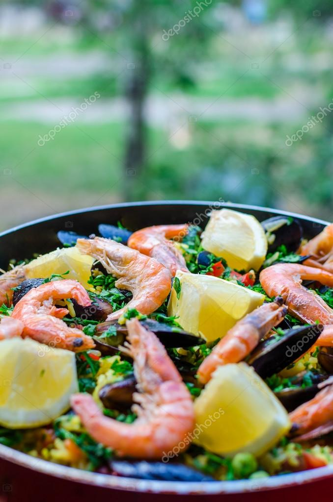 Close up classic seafood paella with mussels, shrimps and vegetables