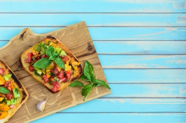 Italian bruschetta with chopped tomatoes and basil on wooden cutting board
