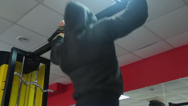 man wearing hoodie doing pull up exercise in gym training hard to