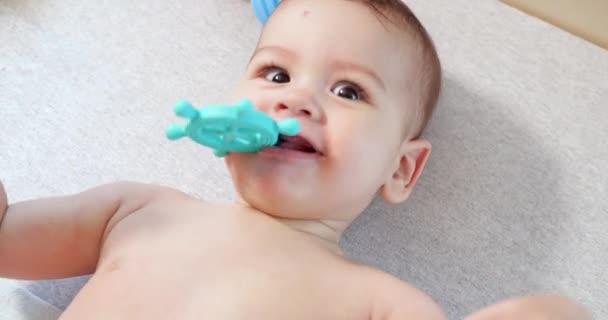 kojenecká, dětská koncepce - detailní záběr šťastného usměvavého miminka si hraje s popruhem. Řezání zubů. První zuby. Joy bezzubý 7 měsíců dítě kousnutí, kousá zuby hračka