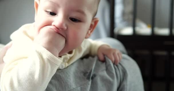 mladá matka drží krásného sedmiměsíčního syna, který se usmívá a hlodá prsty a matčiny ruce. svědivé zuby novorozence, zoubkování