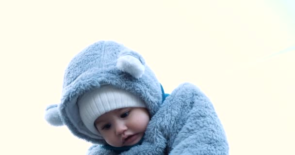 Happy mother playing with little son . Young caucasian mom and baby boy having fun outdoor in winter. slow motion