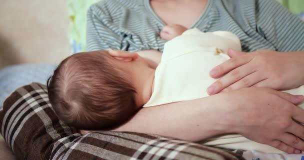 Mutter stillt ihr Neugeborenes auf dem Sofa. Milch von der Mutterbrust ist eine natürliche Medizin für das Baby. Familie, Essen, Kind, Essen und Elternschaft Konzept. Zeitlupe