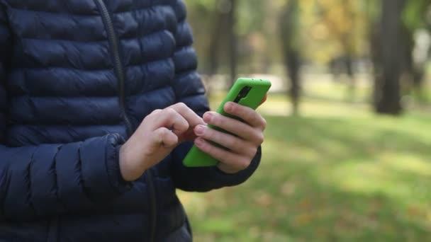 Közelkép egy fiatal fickóról, aki okostelefont tart, és ujjal csúszik a képernyőn. Man olvasás telefon üzenet vagy letölthető egy alkalmazás a mobiltelefonjára.